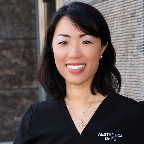 Your Dentist in Seattle, WA - Dr. Fu - Smiling in her scrubs welcoming you to her dental office
