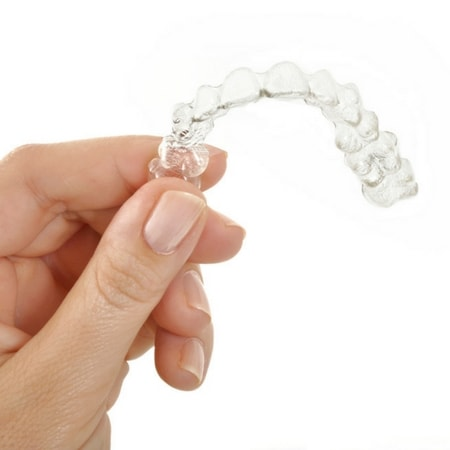 A person holding a MTM Clear Aligner for teeth straightening