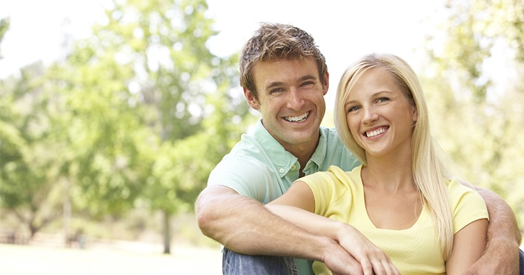 A man and woman sitting and smiling after a cosmetic dentistry procedure at Aesthetica Contemporary Dentistry
